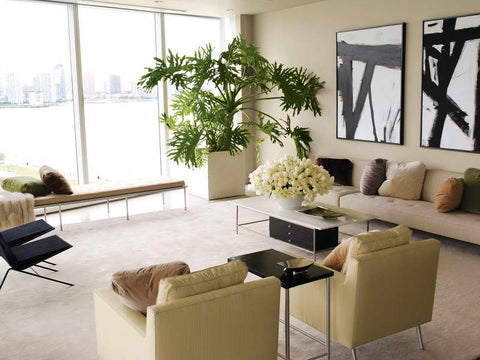 MODERN LIVING ROOM WITH BIG POTTED PLANT AND OPPULENT FLOWER ARRANGEMENT