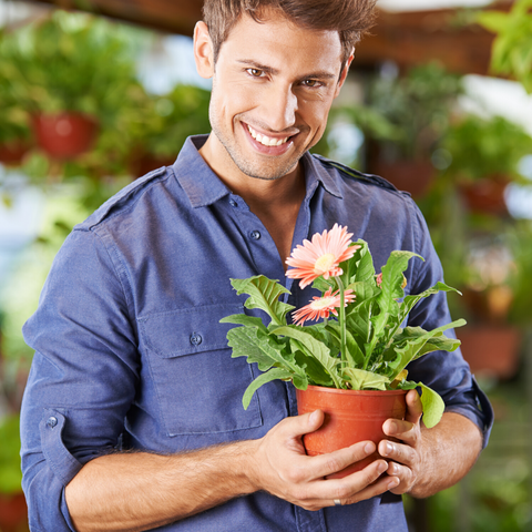 man holding a pot with flowers