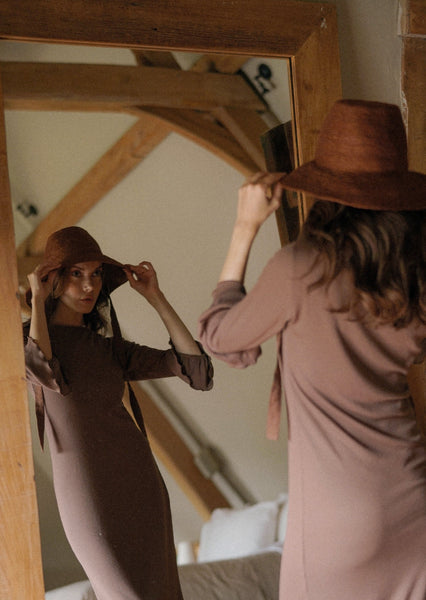 BEAUTIFUL WOMAN WEARING A BROWN DRESS AND A BROWN HAT LOOKING INTO A MIRROR