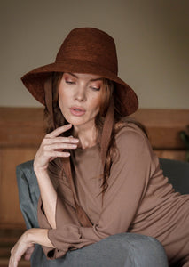 BEAUTIFUL WOMAN IN BROWN HAT ON A GREY CHAIR