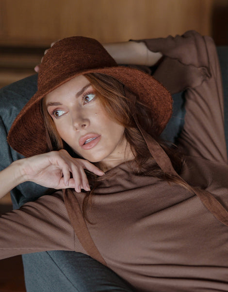 BEAUTIFUL WOMAN WITH BROWN EYES WEARING A BROWN SHIRT AND A BROWN HAT ON A GREY CHAIR