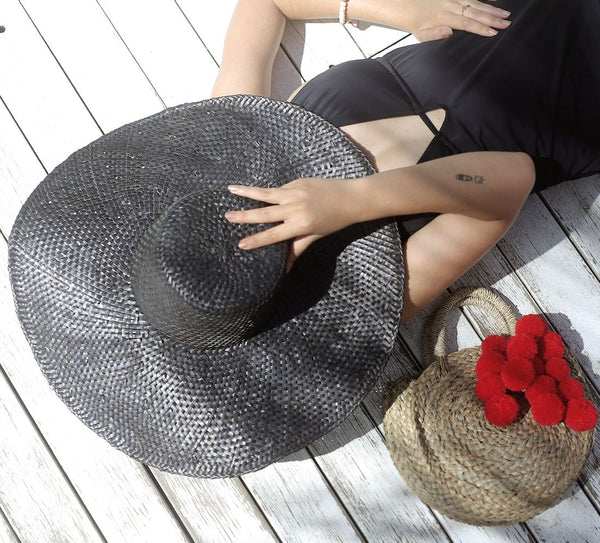 WOMAN IN A BLACK HAT LAYING ON A DECK NEXT TO A STRAW BAG WITH RED POM POMS