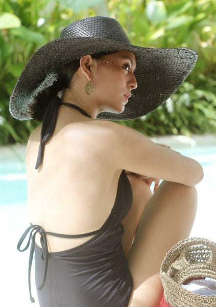 WOMAN IN A BLACK HAT AND BLACK ONE PIECE IN FRONT OF SOME PLANTS