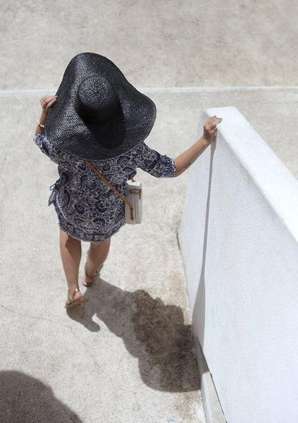 WOMAN IN BLACK HAT STANDING BY A WALL