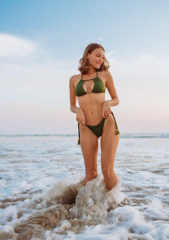 WOMAN STANDING IN THE OCEAN WEARING A GREEN BRAZILIAN BIKINI