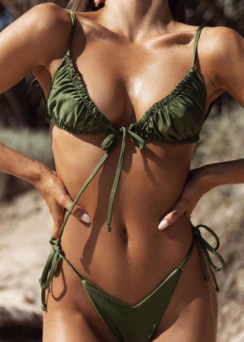 TAN WOMAN WEARING AN OLIVE COLORED BIKINI OUTSIDE