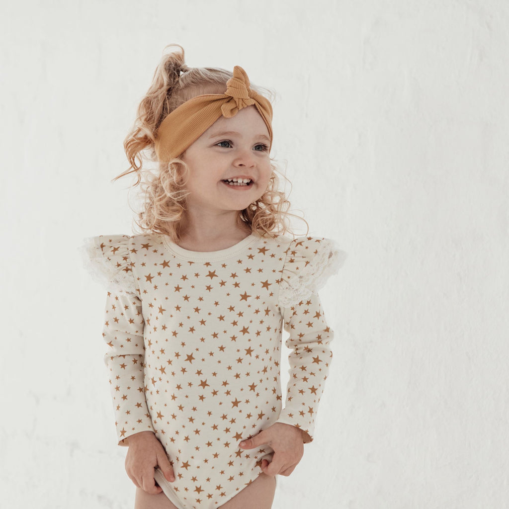 Aster & Oak Organic Lace Girls Taffy Star AOP Onesie close up