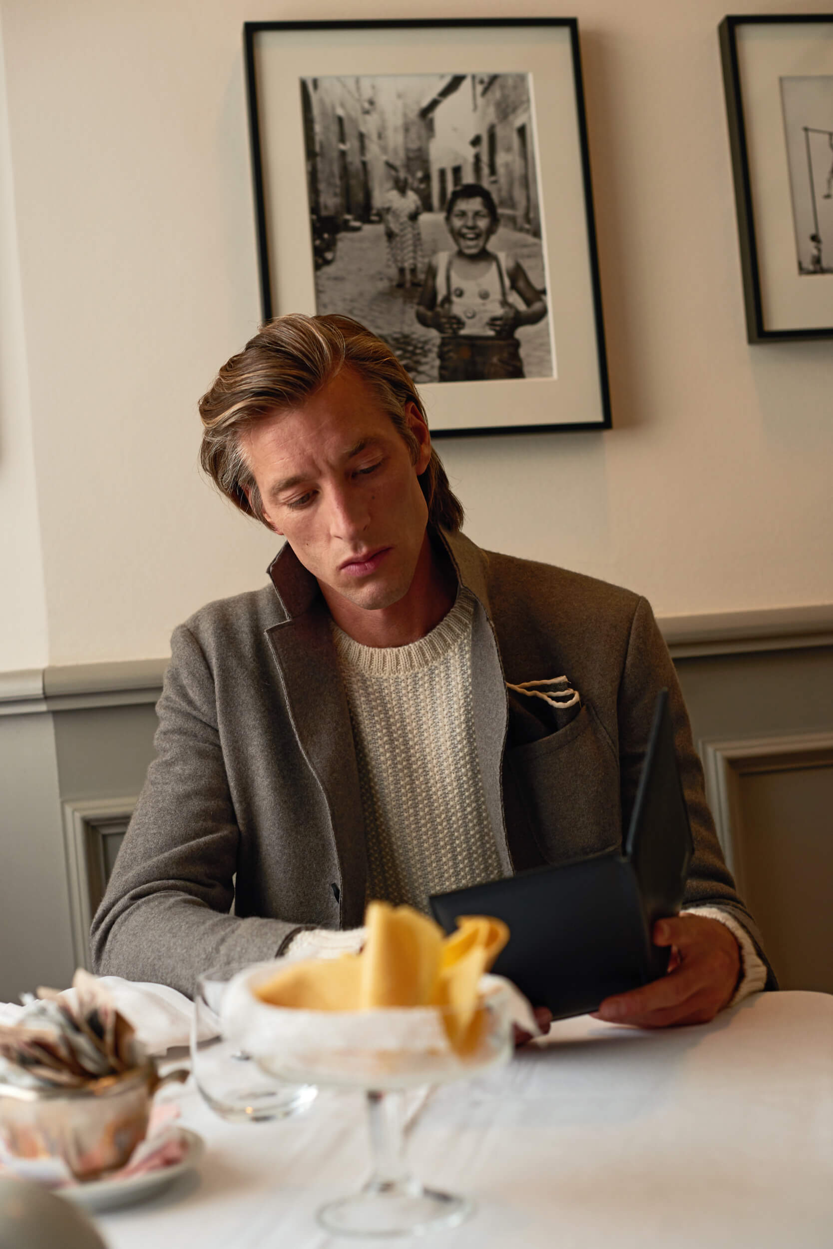 Elengant man sitting at a cafe table with cashmere blazer