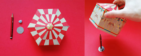 make shift card spinning stand from a pencil, coin and bluetac on a red backdrop