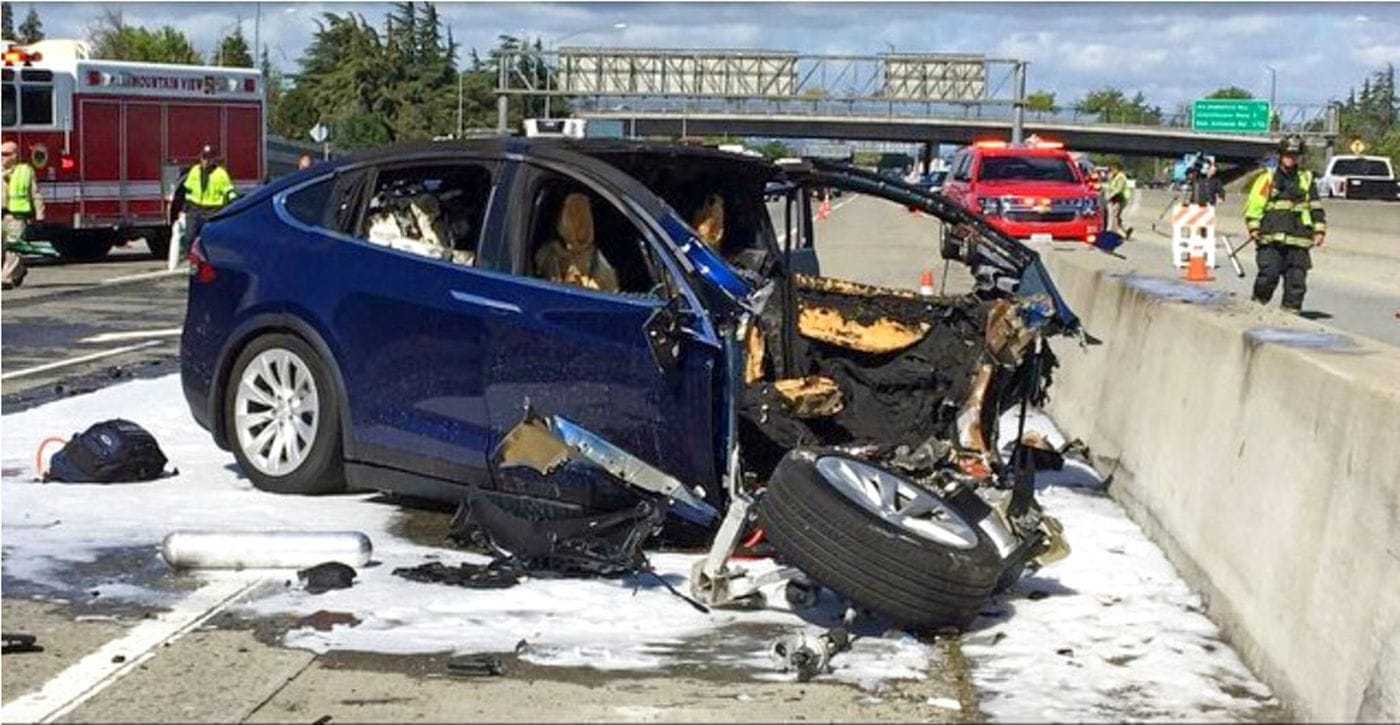 FILE - In this March 23, 2018, file photo provided by KTVU, emergency personnel work a the scene where a Tesla electric SUV crashed into a barrier on U.S. Highway 101 in Mountain View, Calif. The National Transportation Safety Board says the driver of a Tesla SUV who died in a Silicon Valley crash two years ago was playing a video game on his smartphone at the time. Chairman Robert Sumwalt said at the start of a hearing Tuesday, Feb. 25, 2020 that partially automated driving systems like Tesla's Autopilot cannot drive themselves. Yet he says drivers continue to use them without paying attention.