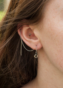 A sterling silver chain threader earring with a 6mm silver circle attached. The earring threads through  different piercings on the ear.