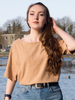 A close-up photograph of a model wearing a silk noil top which has been dyed with dock root. The top has elbow length sleeves and a round neck. The model wears it tucked into denim jeans.