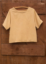 Load image into Gallery viewer, A top dyed yellow with dock leaves hangs on a wooden and metal hanger on the back of an old wooden door. The top has a round neck, and mid length sleeves.