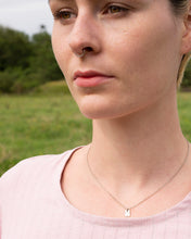 Load image into Gallery viewer, A tiny little initial pendant in sterling silver is worn by our model Emily. The pendant piece is worn close to the neck and hangs on a fine sterling silver chain.