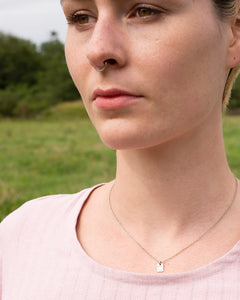 A tiny little initial pendant in sterling silver is worn by our model Emily. The pendant piece is worn close to the neck and hangs on a fine sterling silver chain.