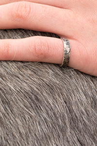 A model wears a sterling silver ring with a hammered texture. The ring has been blackened and then polished which results in a mottled appearance.