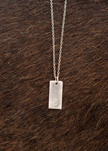 Load image into Gallery viewer, The ampersand logo is stamped onto a rectangular pendant of sterling silver. The pendant hangs from a sterling silver chain.