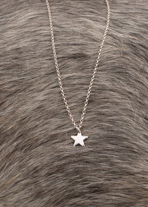 A close up image of our silver star pendant, which comprises of a small sterling silver star on a sterling silver chain, which is available in different lengths.