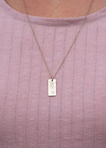 A rectangular pendant in sterling silver with the ampersand logo stamped onto it. The silver has a scratched finish, and is available on different length chains.