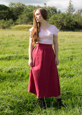 Our model Katie wears a v-necked, short sleeved t-shirt in pale pink linen.