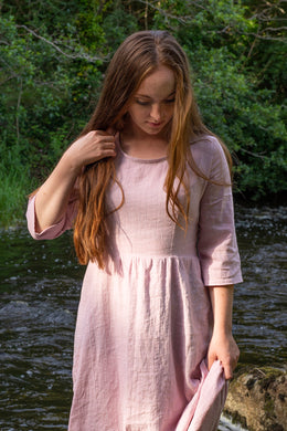 Katie stands at a river wearing a long pink linen dress, with a fitted bodice and wide, gathered skirt.