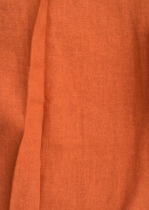 A close-up photograph of the burnt orange linen fabric.