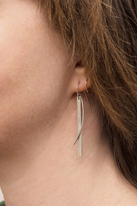 A long sterling silver drop earring consisting of a thin rectangle being hugged by a curved silver wire.