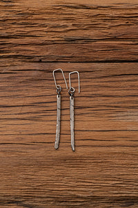 Sterling silver drop earrings, featured a long, thin piece of sterling silver which has been scored diagonally in places. The silver has been blackened in places to add depth and texture.
