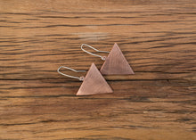 Load image into Gallery viewer, Copper triangle earrings hanging from sterling silver ear hooks. The copper has a scratched matt finish. The triangles have side measurements of 35mm each.