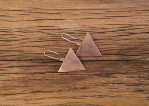 Copper triangle earrings hanging from sterling silver ear hooks. The copper has a scratched matt finish. The triangles have side measurements of 35mm each.