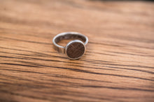 Load image into Gallery viewer, A sterling silver band with a setting containing a circle of walnut. This circle has been scorched and engraved with lines.