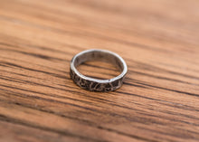 Load image into Gallery viewer, A sterling silver ring with a hammered finish.  The recesses are blackened, giving the ring a mottled appearance. The silver has a thickness of 1.3mm, and a height of 4.5mm.