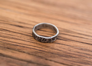 A sterling silver ring with a hammered finish.  The recesses are blackened, giving the ring a mottled appearance. The silver has a thickness of 1.3mm, and a height of 4.5mm.