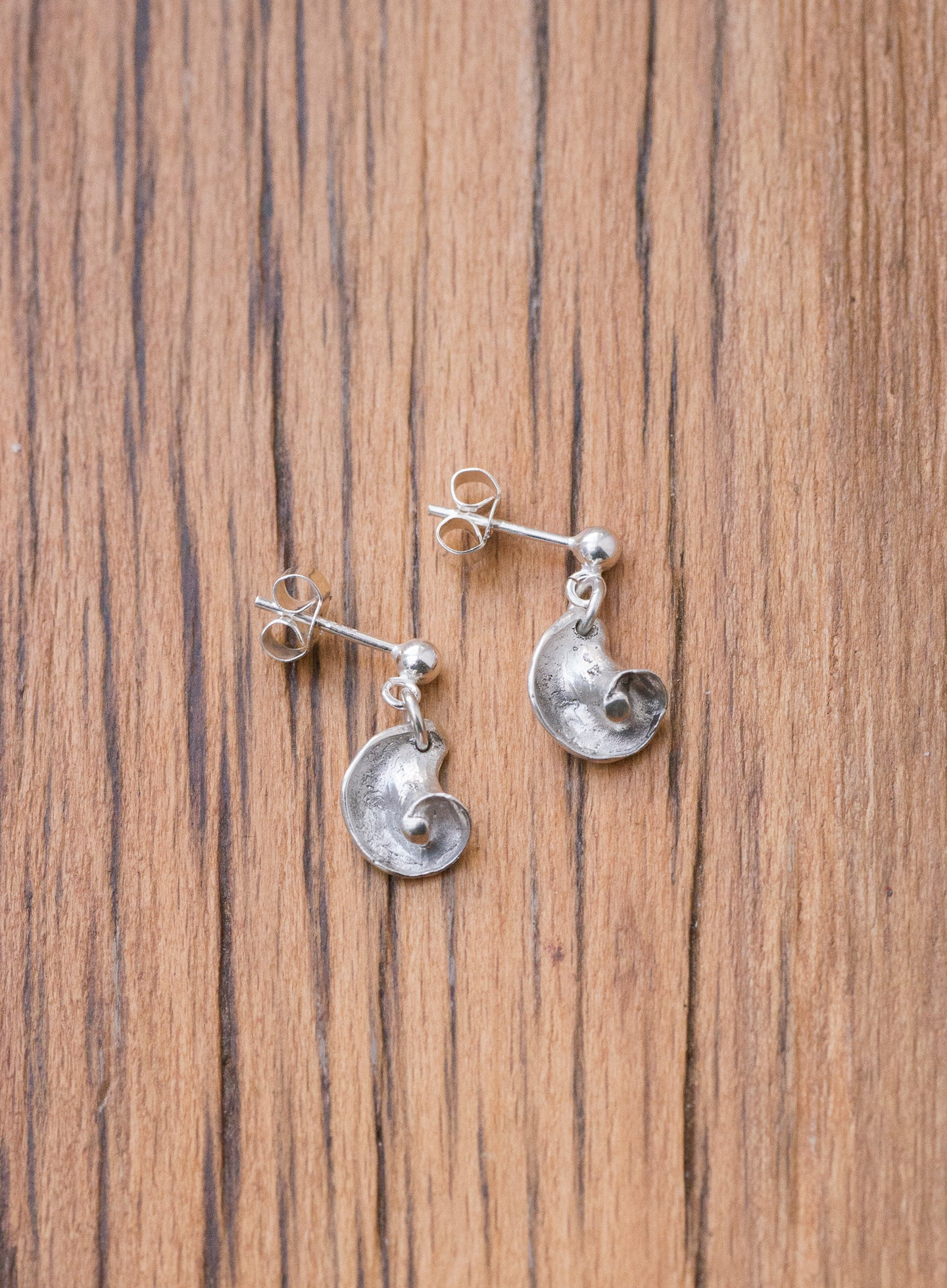 A pair of sterling silver and fine silver earrings in the shape of shells. The shells are dangling from a ball stud, and are set against a wooden background.