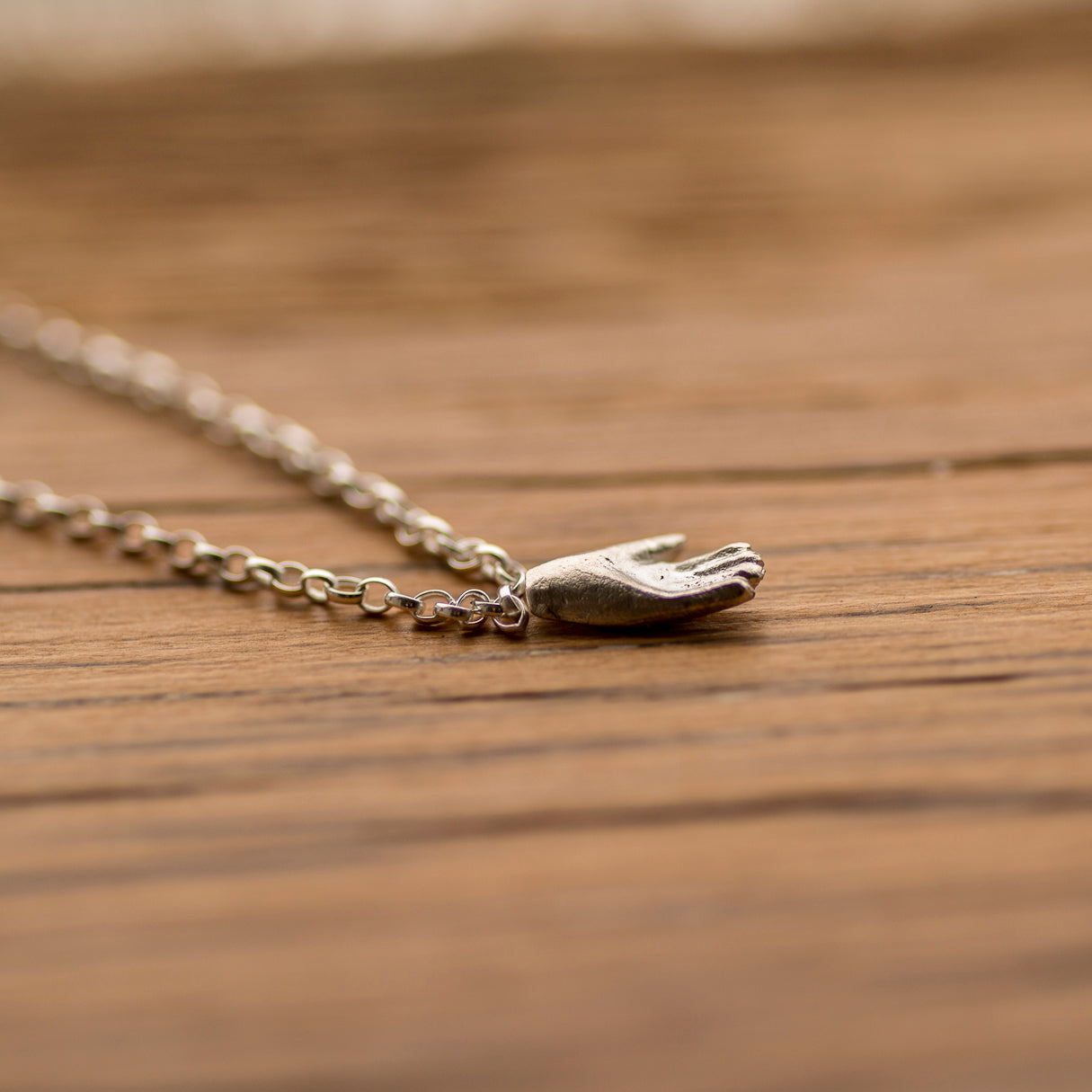 A tiny fine silver hand hanging from a sterling silver pendant, displayed on an oak board. The little hand measures only 11mm, and chains are available in various lengths.