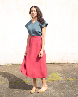 A calf length linen skirt in a rich berry shade. The skirt is gathered at the waist, and has hidden side pockets.