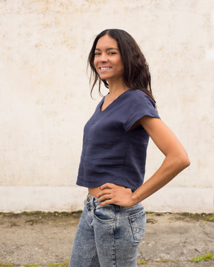 A cap sleeved linen top in midnight blue. There is a v-neck at both back and front, and it is cropped at the waist.