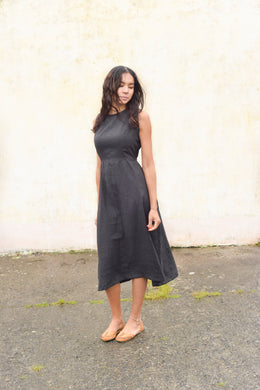 A black linen sleeveless dress with a high neckline. The dress is gathered at the waist, has hidden side pockets, and is calf-length.
