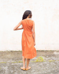 Back view of the burnt orange linen sleeveless dress. This dress is gathered at the waist and is calf-length. It is closed at the back with a salvaged nylon invisible zip.