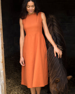 The burnt orange linen sleeveless dress. This dress has a high neckline, is gathered at the waist and is calf-length.