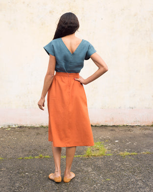A vivid orange calf length skirt which is gathered into a waistband at the waist. It is closed at the back with a nylon invisible zip, and has hidden side pockets.