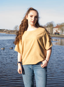 A model stands in front of a river wearing a silk noil mid length sleeve top, dyed a warm yellow with dock leaves. This top is loose fitting with a hem between the waist and hips.