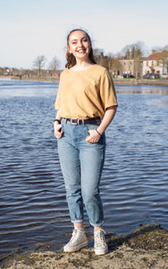 A model is pictured in front of a body of water. She wears a warm yellow top which has been dyed with dock leaves. The top is loose fitting, with elbow length sleeves, and is tucked into a pair of jeans at the waist.