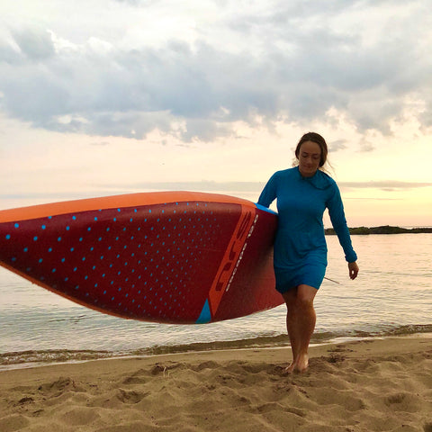 Young woman carries her inflatable Stand Up Paddle Board across a Lake Superior Beach