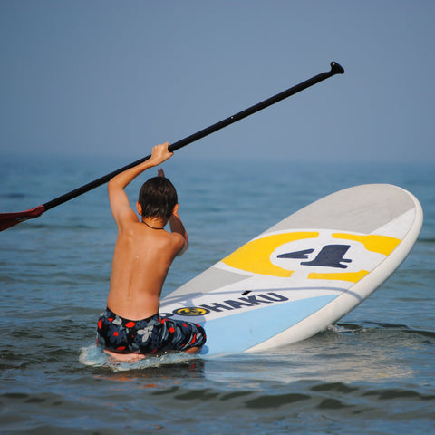 Child sits while paddling an All ROunder shaped Stand Up Paddleboard