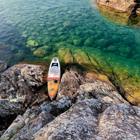 Rigid Stand Up Paddleboard resting on the rocky shore of Lake Superior