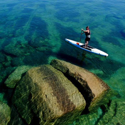 Woman paddles a displacement hull stand up paddleboard above huge rocks on Lake Superior