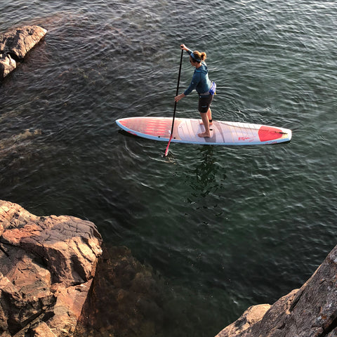 Young woman paddles a hybrid shaped stand up paddleboard near the rocks in Marquette Michigan
