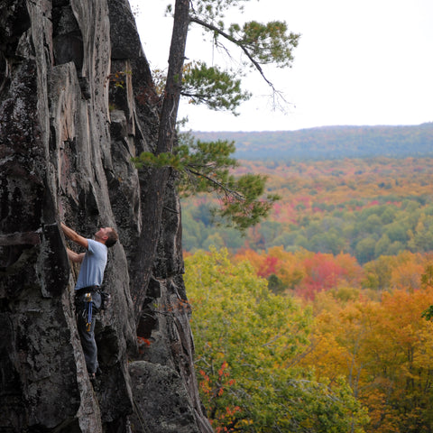 A rock climber at Silver Mountain Michigan during fall colors
