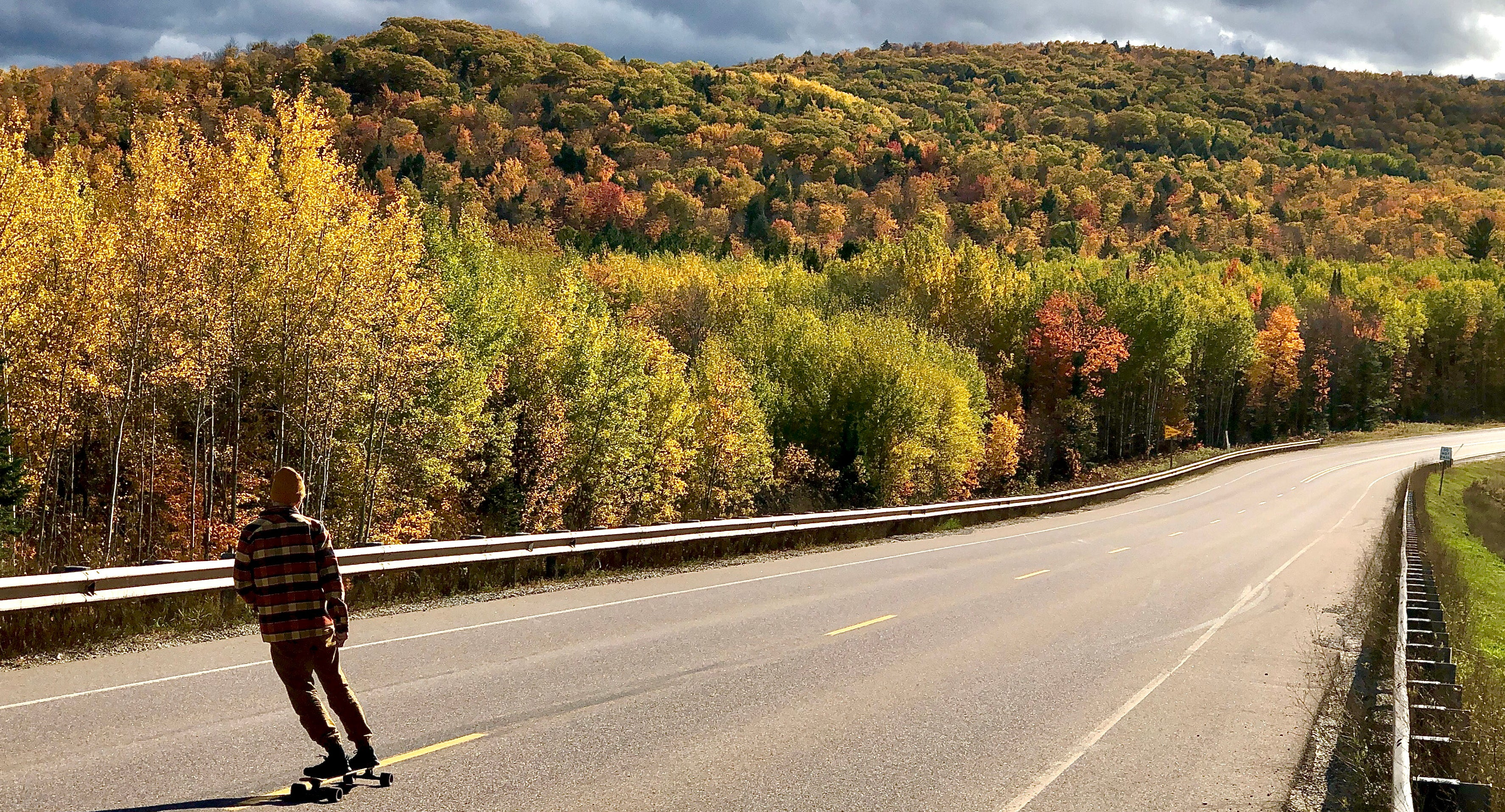 Longboarding downhill on a fall day in the Upper Peninsula
